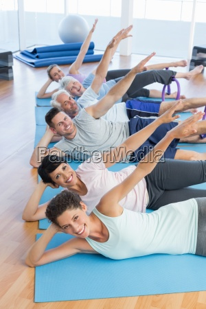 fitness class stretching legs and hands