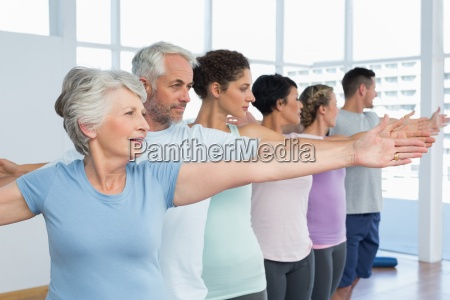 class stretching hands in row at