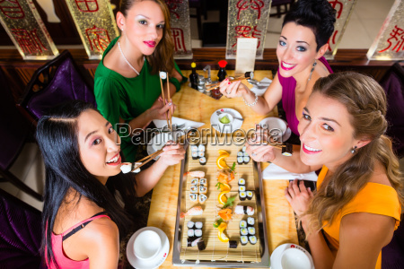 women eating sushi in asian retaurant