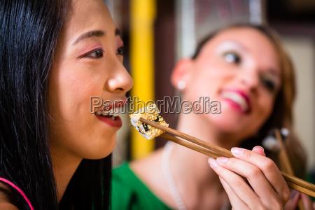 women eating sushi in asian retaurant