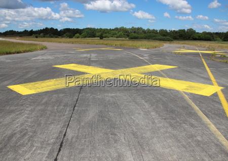 gelb lackiertes kreuz auf asphalt mit