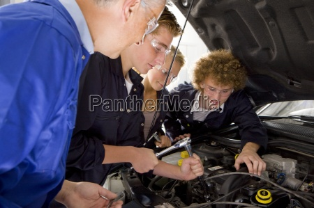 teacher watching students repair car in