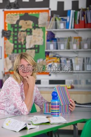 smiling teacher sitting at desk in