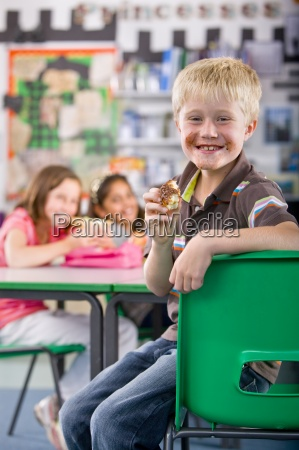smiling boy eating chocolate donut in