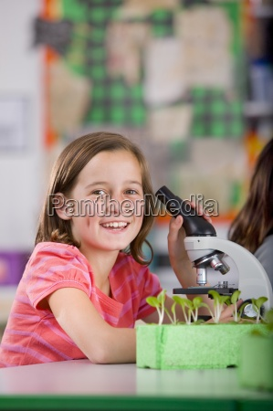 smiling student with microscope in science
