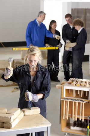 student hammering chisel in bricklaying vocational