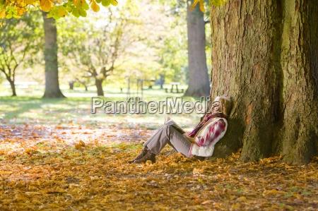 happy senior woman reading book under