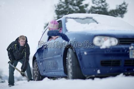 woman in car watching man shoveling