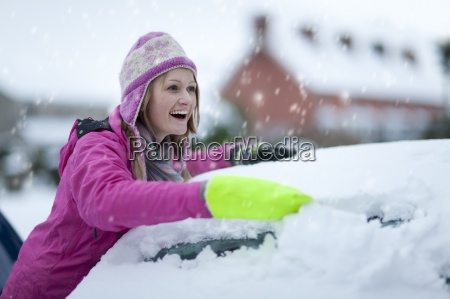 smiling woman scraping snow from car