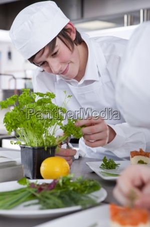 trainee chef working with parsley in