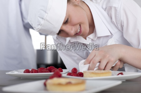 trainee chef wiping gourmet dessert in