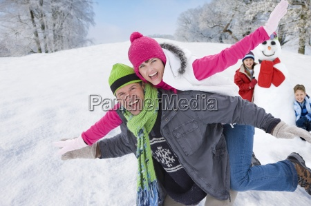 man carrying exuberant woman on back
