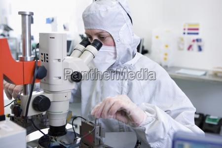scientist in clean suit examining silicon