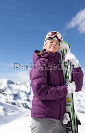 woman with eyes closed holding skis