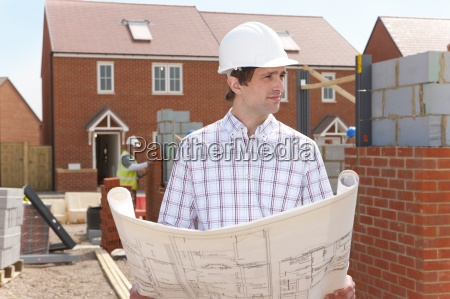 architect holding blueprints at housing construction