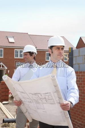 architects holding blueprints at housing construction