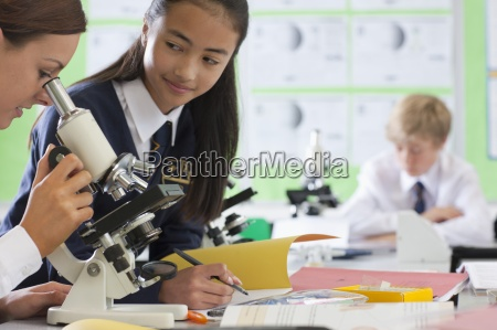 students in school uniforms using microscopes