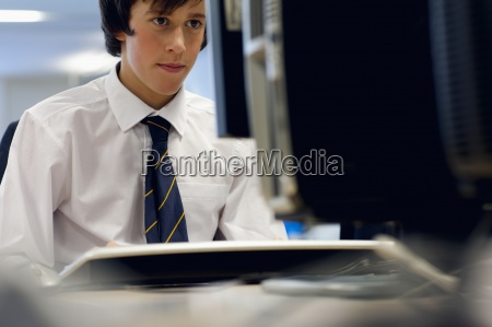 male student in school uniform using