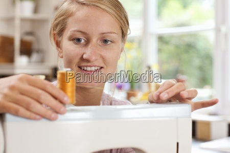 smiling young woman attaching thread to