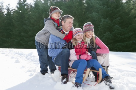 happy family sitting on sled in