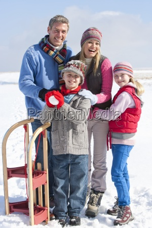 portrait of smiling family with snowball
