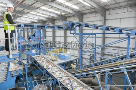 businessman on platform above conveyor belts