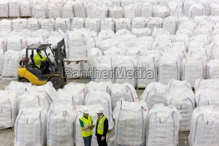 businessman and workers among large bags