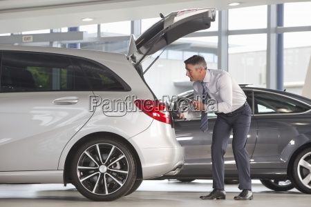 man with brochure looking into hatchback