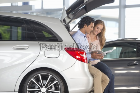 couple looking at brochure in hatchback