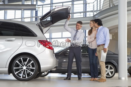 salesman and couple looking into hatchback