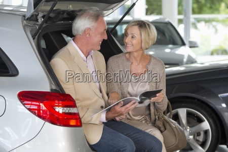 smiling couple looking at brochure in