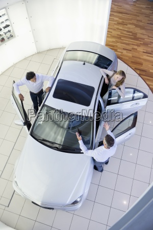salesman and couple looking inside car