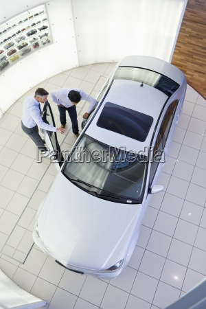 salesman and customer looking inside car