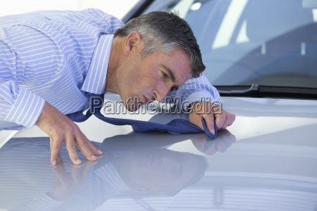 salesman wiping automobile hood with tie