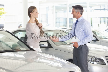 salesman and customer shaking hands in