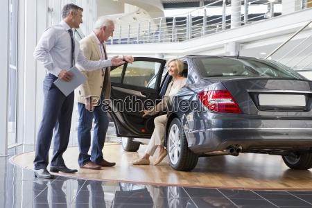 salesman and couple looking at car