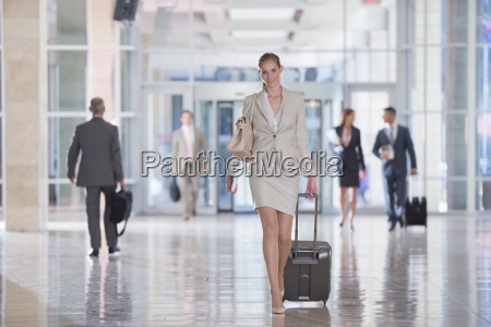 portrait of smiling businesswoman pulling suitcase