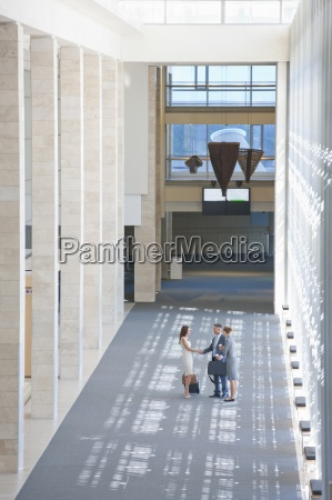 business people handshaking in lobby of