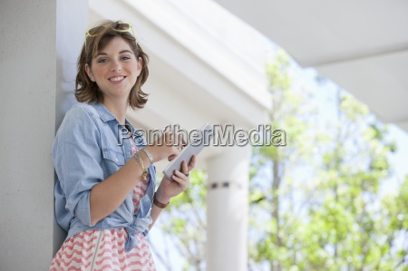portrait of smiling young woman using
