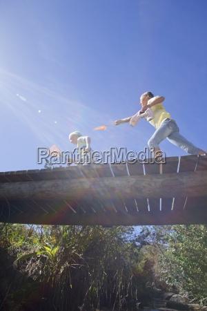 girl chasing boy with fishing net