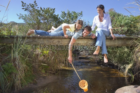 family laying on footbridge and dipping