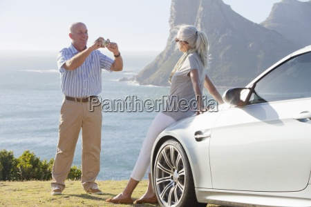 man photographing woman leaning against car