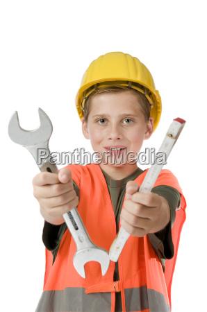 boy with helmet holding tools