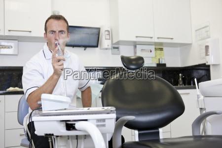 ein maennlicher zahnarzt in seiner praxis