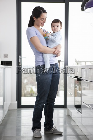 a mother standing in a kitchen