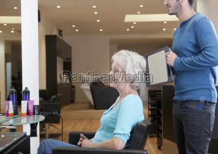 a meski fryzjer pokazujac jego klient