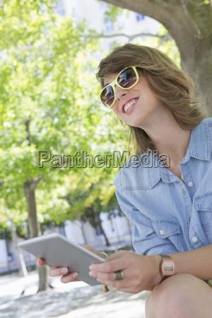 laechelnde junge frau traegt eine sonnenbrille