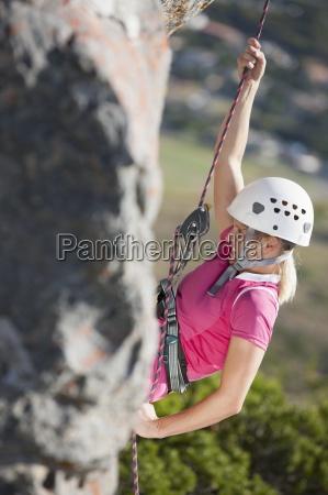 weibliche kletterer aus seil haengend