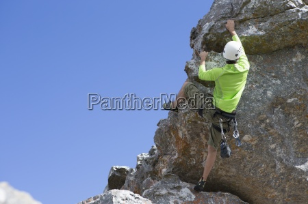 male rock climber hanging from rock
