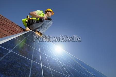 techniker installieren solarpanel auf dem dach